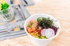Traditional Hawaiian dish poke bowl with fork. Hawaiian salmon fish with rice, radish,cucumber, tomato, sesame seeds and. Seaweeds. Diet and Useful fast food stock photo