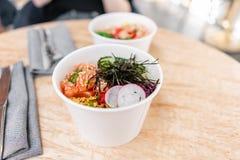Traditional Hawaiian dish poke bowl with fork. Hawaiian salmon fish with rice, radish,cucumber, tomato, sesame seeds and. Seaweeds. Diet and Useful fast food stock images