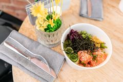Traditional Hawaiian dish poke bowl with fork. Hawaiian salmon fish with rice, radish,cucumber, tomato, sesame seeds and. Seaweeds. Diet and Useful fast food royalty free stock photo