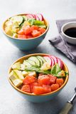 Traditional Hawaiian Poke salad with salmon, avocado rice and vegetables in a bowl on two persons. Top view stock photography