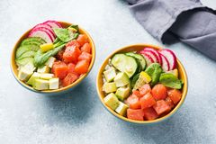 Traditional Hawaiian Poke salad with salmon, avocado rice and vegetables in a bowl on two persons. Top view stock photos
