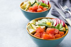 Traditional Hawaiian Poke salad with salmon, avocado rice and vegetables in a bowl on two persons. Copy space. Traditional Hawaiian Poke salad with salmon stock images