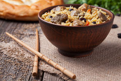 Traditional healthy asian national spicy rice food. Pilaf cooked with fried meat, onion, carrot and garlic. Served in rustic clay bowl on vintage wooden table Royalty Free Stock Images