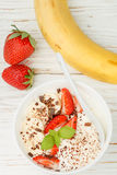 Traditional healthy Breakfast. Natural yogurt with strawberries, banana and chocolate Stock Photos
