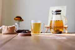 Traditional heral tea with glass teapot, cup, dried rose buds. Flowers on wooden table at home,sunlight background royalty free stock image