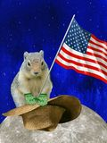 Traditional holiday Groundhog Day. On the blue starry sky the moon, a groundhog flying over it in a hat holding an American flag in its paws stock photography