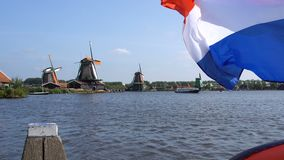 Traditional Holland Windmills and Floating Flag in Zaanse Schans, Netherlands. Touristic Village near the Amsterdam with stock video