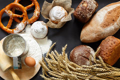 Traditional home bread and wheat. On the black background royalty free stock photo