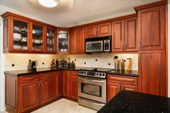 Traditional Home Kitchen. Traditional cheery wood cabinet home kitchen with a black granite countertop royalty free stock image