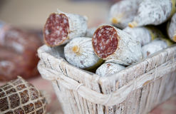 Traditional home-made salami in the basket on the market for sale. Stock Photos