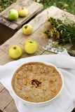 Traditional homemade American apple pie, apples and bouquet of wildflowers on a wooden background. Rustic style. stock photo