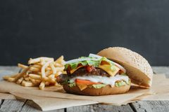 Traditional homemade burger on baking paper. With french fries stock photo