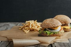 Traditional homemade cheeseburgers on baking paper. With french fries stock photo