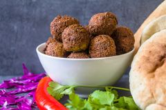 Traditional homemade chickpea Falafel balls in a bowl with coriander leaves & seeds, red pepper & cabbage, pitta bread stock photo