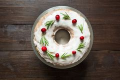 Homemade Christmas cake with garnish cranberry and rosemary on decorative plate. Top view royalty free stock images