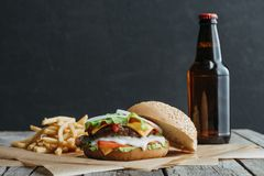 Traditional homemade hamburger, french fries and bottle of beer on baking paper. On wooden tabletop stock photos