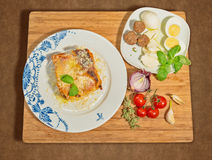 Traditional homemade lasagna,accompanied with meatballs,boiled eggs,onions,tomatoes and aromatic herbs. Stock Photos
