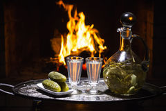Traditional homemade russian  vodka. With fireplace on background Stock Photography