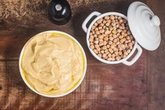 Traditional hommos in a bowl. Over a wooden table Stock Photo