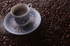 Traditional hot coffee cup with beans and smoke steam over a bla Royalty Free Stock Photography