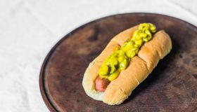 Traditional hot dog with gherkin and mustard relish against white background. Hot dog with gherkin and mustard relish against white background royalty free stock photo