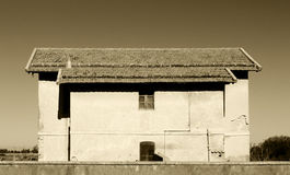 Traditional house, background, high constrast. A front view of a traditional house, with large roofs covered with tiles, high contrast sepia picture, landscape royalty free stock images