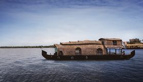 A traditional house boat is anchored on the shores of a fishing lake in Kerala`s Backwaters, India. - Image stock image