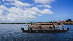 A traditional house boat is anchored on the shores of a fishing lake in Kerala`s Backwaters, India. - Image stock photo