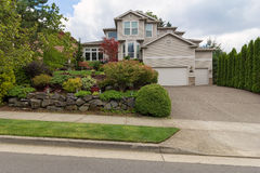 Traditional House in North America Suburbs. Traditional house with three car garage frontyard garden lush landscaping and green lawn in North America suburban royalty free stock photo