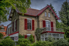 Traditional house with red shutters Royalty Free Stock Photos