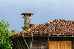Traditional house in Zheravna, Bulgaria. Clay tile roof and chimney made of stone bricks, Zheravna village, Bulgaria Royalty Free Stock Images