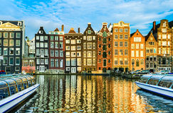 Traditional houses of Amsterdam, Netherlands. Traditional houses of Amsterdam with boats and reflections in the water Stock Photo