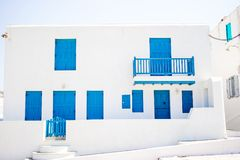 Traditional houses in the narrow streets of Mykonos, Greece. Traditional houses with blue doors and windows in the narrow streets of Mykonos, Greece Royalty Free Stock Image