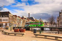 Traditional houses, bridge and people in Leiden, Netherlands. Leiden, Netherlands - April 7, 2016: Street view with traditional houses, bridge and people in stock photos