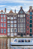 Traditional houses and a cruiseboat at the Damrak in Amsterdam Stock Photos