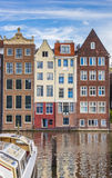 Traditional houses and a cruiseboat at the Damrak in Amsterdam Royalty Free Stock Photo