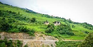 Mountain scenery in Bhutan. Traditional houses on the hill with many platations in Bhutan Royalty Free Stock Image