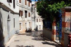 Traditional houses in Veli Losinj island in Croatia. Stone paved street in Veli Losinj island in Croatia Royalty Free Stock Image