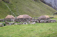 Traditional Housing in High-Elevation Peru. Stone houses with grass roofs, and surrounding stone walls, are commonly seen at very high elevations in Peru, such Stock Photos