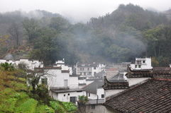 Traditional Hui style architecture in a foggy day in Wuyuan County-Jiangxi province-China. Traditional well-preserved ancient Hui style architecture in Wuyuan Stock Photos