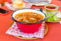 Traditional Hungarian fish soup in red kettle stock photos
