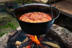Traditional Hungarian Goulash soup in cauldron. Meal cooked outdoors on an open fire. delicious and healthy food popular in Central Europe Stock Photos