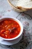 Traditional Hungarian hot goulash soup with bread, background is traditional grey embroidery lace table. Royalty Free Stock Photo