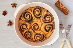Traditional Hungarian pastry for Thanksgiving and Christmas - poppy seed rolls in the baking dish decorated with cinnamon, anise. Cinnamon buns on the gray stock image