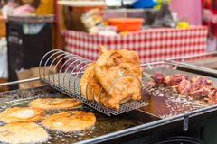 Traditional Hungarian street food Langos frying in boiling oil at fair. stock photo