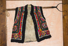 Traditional hutsul sheepskin vest hanging on the wall Stock Photos