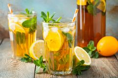 Traditional iced tea with lemon and ice in tall glasses on a wooden rustic table.  stock photo