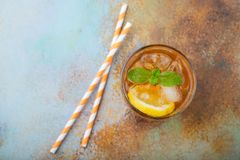 Traditional iced tea with lemon, mint and ice in tall glasses. A glass of refreshing summer drink on the old rusty background. Top stock image
