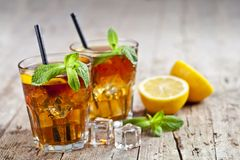 Traditional Iced Tea With Lemon, Mint Leaves And Ice Cubes In Glasses On Rustic Wooden Table Stock Photos