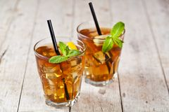 Traditional Iced Tea With Lemon, Mint Leaves And Ice Cubes In Two Glasses On Rustic Wooden Table Stock Images